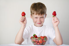 Boy with strawberries. Little funny boy with strawberries Royalty Free Stock Images