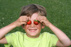 The boy with a strawberry. The boy plays with strawberry Stock Images