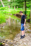 Boy at Stream. An 11 year old boy standing on the rock in a stream Royalty Free Stock Photo