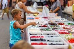 Boy on street fruit market in SPain. Boy on summer street fruit market in SPain royalty free stock photo