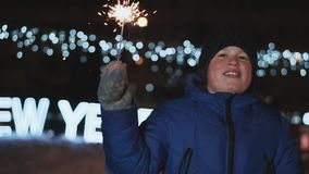 The boy on the street, New Year`s Eve. He holds a sparkler and rejoices