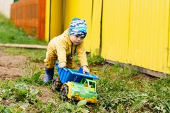 The boy in yellow suit playing with a toy car in the dirt. The boy in the street playing with a toy car stock photo