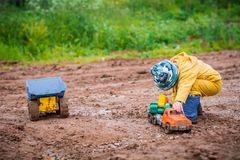 The boy in yellow suit playing with a toy car in the dirt. The boy in the street playing with a toy car royalty free stock image