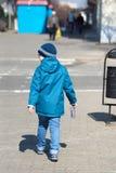 Boy on street. Warmly dressed boy is walking along a city street Royalty Free Stock Photo