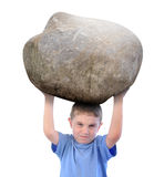 Boy with Stress Holding a Rock. A young boy is holding up a heavy rock and looks stressed about the burden. There is a white isolated background Stock Photo