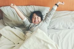 Boy stretching on the bed stock photography