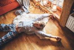 Boy stretching himself lying on floor on sheepskin and looking in window in cozy home atmosphere. Peaceful Lazy moments in cozy. Home concept image stock photos