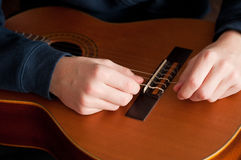 Boy strings his acoustic guitar, close up Royalty Free Stock Images