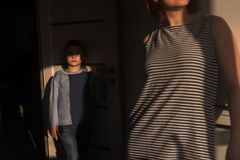 A boy in a striped jacket and jeans is upset in the room because he quarreled with mother and does not find support stock image
