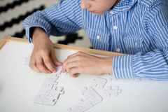 Boy doing puzzles. Boy in striped shirt is doing puzzles on white desk at home. Autistic child therapy concept Stock Image
