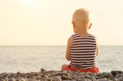 Boy in striped t-shirt sitting on the beach. Back view Stock Image