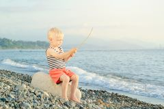Boy in a striped T-shirt is sitting on the beach with a wand. Sea in the background Stock Photos