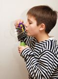 Boy in striped vest and a big soap bubble Royalty Free Stock Photos