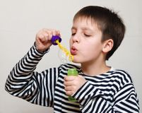 Boy in striped vest and bubbles. Boy in striped vest blows soap bubbles intently Stock Photography