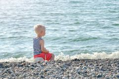 Boy in striped vest sits on a rock by the sea. Back view Stock Photography