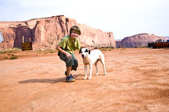 Boy strokes a dog in the landscape of Monument Valley Royalty Free Stock Photography