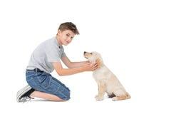 Boy stroking dog while kneeling Royalty Free Stock Image