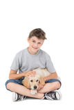 Boy stroking dog while sitting over white background Royalty Free Stock Images