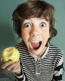 Boy with strong white teeth bite apple Stock Image