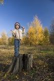Boy on stub in autumn park Stock Photos