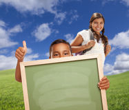 Boy student gives Thumbs Up Holding Blank Chalk Board. Hispanic Students with Thumbs Up in Grass Field Holding Blank Chalk Board Stock Photography