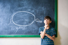 Boy Student Leaning On Blackboard And Thinking In Classroom Stock Photo