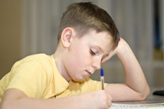 A boy student learns lessons. While sitting at a desk royalty free stock photos