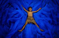A boy in student pants school uniform sleep or playing on floor. At playground blue blackground, he believe can fly, countryside Thailand stock images