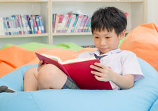 Boy student reading book in library. Asian boy student in uniform reading book in school library Royalty Free Stock Photo