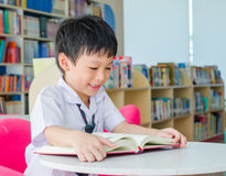 Boy student reading book in library Stock Photos