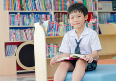 Boy student reading book in library. Asian boy student in uniform reading book in school library Stock Photography
