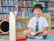 Boy student reading book in library Stock Images