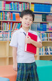 Boy student reading book in library Stock Image