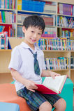Boy student reading book in library Royalty Free Stock Images