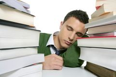 Boy student sleeping over stack books over desk Royalty Free Stock Photography