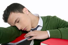 Boy student sleeping over stack books over desk Stock Photo