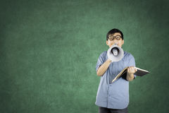 Boy student using a megaphone to speak. Boy student learning with a book while using a megaphone to speak at the camera with copy space in the class Royalty Free Stock Photos