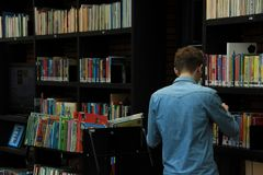 The boy, student, is working and put the book back in the bookcase in the municipal library. Royalty Free Stock Images