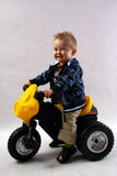 Boy in the studio. Smart boy with motobike toy in the studio having fun Stock Photography