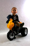 Boy in the studio. Smart boy with motobike toy in the studio having fun Royalty Free Stock Images