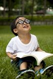 Boy study on the green grass. Happy asian boy study on the green grass Royalty Free Stock Images