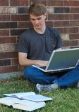 Boy Studying. A college-age boy on a laptop computer sitting outside in the grass studying with books Royalty Free Stock Photos
