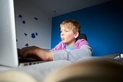 Boy Studying In Bedroom Using Laptop Royalty Free Stock Image