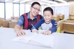 Boy studying in the class with male tutor. Male elementary school student studying in the classroom and write on the book with male tutor Stock Photography