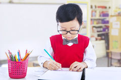 Boy studying in classroom Stock Images