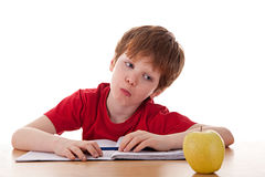 Boy studying and distracted with an apple. Isolated on white background Stock Photography
