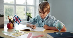 Boy studying english in classroom. Teenage boy in shirt reading book in english, british flag standing on table, modern education stock footage