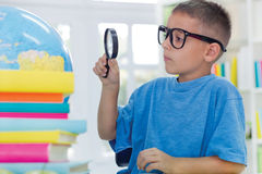 Boy studying geography. Little boy studying geography with a magnifying glass Stock Photos