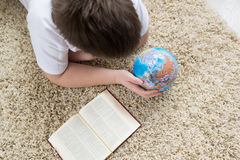 Boy studying the globe and reading  book Stock Photos