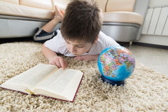 Boy studying the globe and reading  book Royalty Free Stock Photography